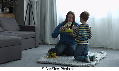 Cute liitle son giving a gift to her happy mother