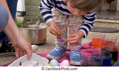 Cute little 3 year old girl selecting dyed colored easter eggs from a crate