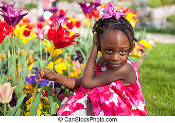 Cute little african american girl playing in the garden