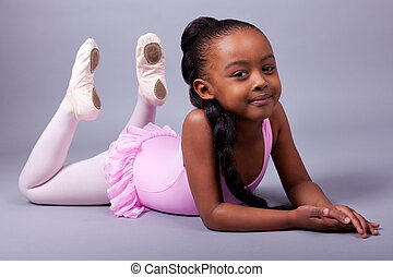 Cute little African American girl wearing a ballet costume...