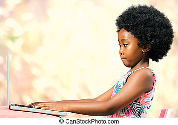 Cute little african girl with afro hairstyle typing on laptop.