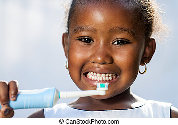 Close up portrait of cute little afro girl holding electric toothbrush ready to brush teeth.