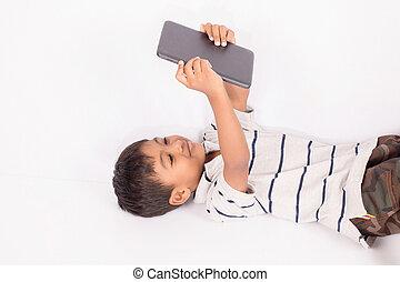 Cute little asian boy lying play tablet on floor