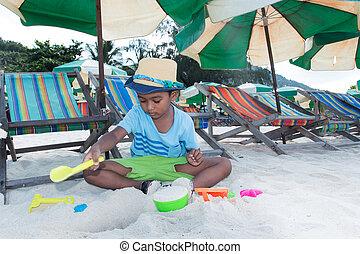 Cute little asian boy play sand on the beach