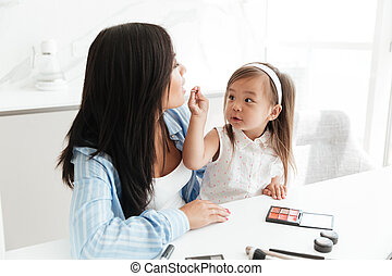 Cute little asian girl doing make up for her mother and...