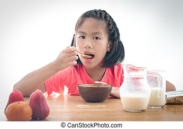 cute little Asian girl eating cereal with the milk on white background