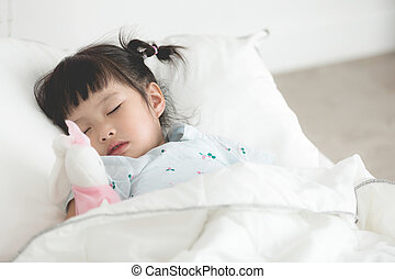 Cute little asian girl sleeping with doll in bed