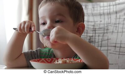 Cute little baby alone eats porridge with a spoon from a plate, the concept of healthy eating.