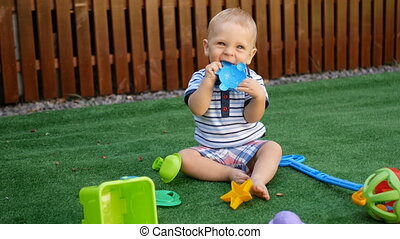 Cute little baby boy, playing with toys outdoors, sunny kids.