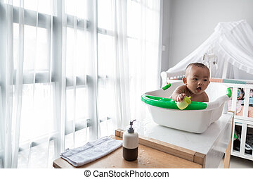 baby boy taking a bath sitting on a basin