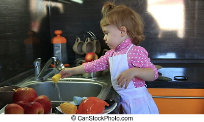 cute little baby dressed as a cook wash in the sink toys in...