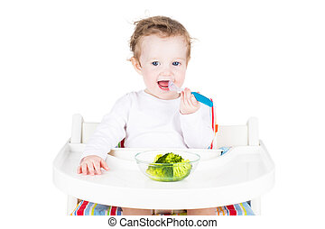 Cute little baby eating broccoli, isolated on white