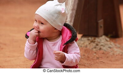 Cute little baby girl dressed in the pink clothing sitting...
