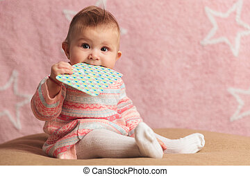 cute little baby girl eating on a card