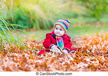 Cute little baby girl in a red coat and knitted colorful hat and