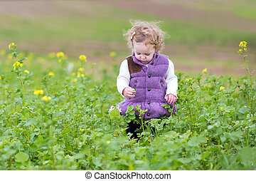 Cute little baby girl in a warm purple jacket playing with flowe