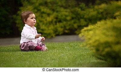 Cute little baby-girl learning to crawl on the green meadow...
