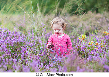 Cute little baby girl playing with purple heather flowers on a n