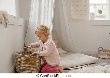 Cute little baby girl plays in a children's room.