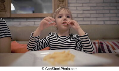 Cute little baby girl sitting at cafe eating delicious french fries
