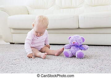 Cute little baby girl wearing pink clothes sitting on carpet