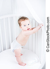 Cute little baby in a diaper standing in a crib