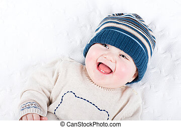 Cute little baby in a knitted hat and sweater