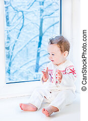 Cute little baby in a knitted sweater with snowflake ornament si