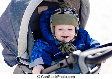 Cute little baby in a stroller outdoor in winter