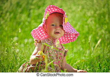 Cute Little baby in hat sitting in the grass - outdoor