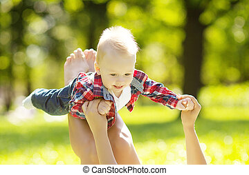 Cute little baby in summer  park with mother  on the grass. Swee