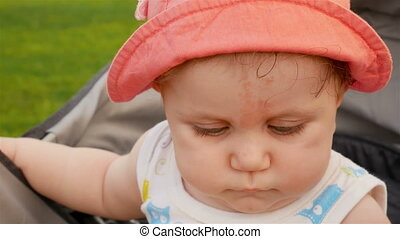Cute little baby is looking To the camera in a red hat. 4k...