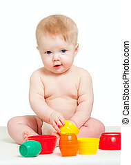 Cute little baby is playing with color toys, isolated over...