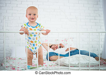 Cute little baby is standing on the edge of bed