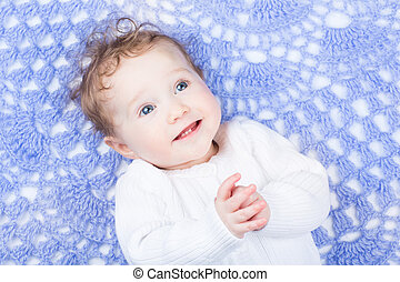 Cute little baby on a hand made knitted blanket