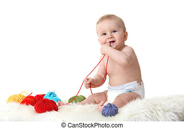 Cute little baby playing with balls of wool isolated on white background
