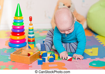 Cute little baby playing with colorful toys