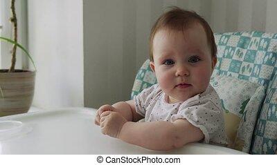 Cute little baby sitting in a children's chair