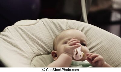Cute little baby sway on swing in apartment. Baby dummy....