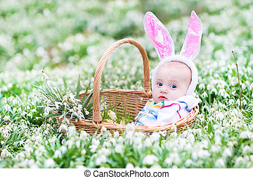Cute little baby wearing bunny ears sitting in a basket