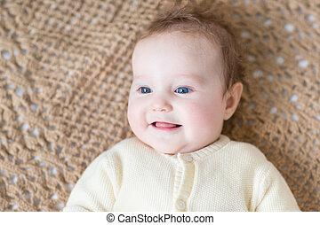 Cute little baby with beautiful blue eyes wearing a warm sweater