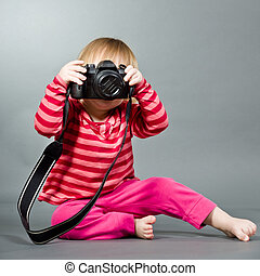 Cute little baby with digital photo camera on gray...