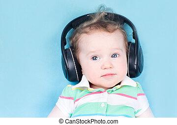 Cute little baby with huge earphones