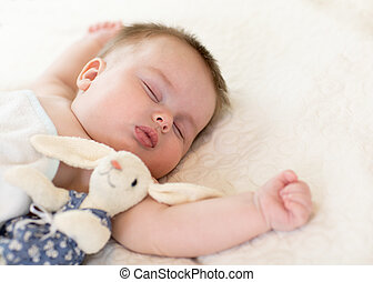 Cute little baby with toy bunny sleeping on bed at home