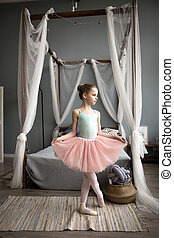 Cute little ballerina in pink ballet costume and pointe shoes is dancing in the room.