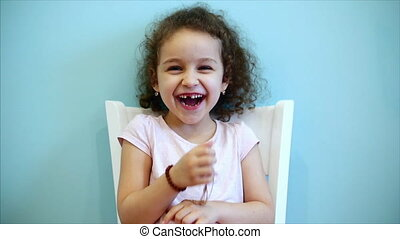 Cute little beautiful funny baby with red curly hair girl sitting on a white chair on a blue background and looking at the camera smiling.