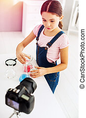 Cute little blogger standing in front of camera making chemistry experiment