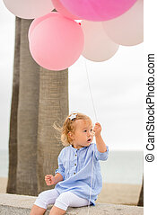 Cute little blond girl holding party balloons