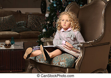Cute little blond girl sitting on background of Christmas tree