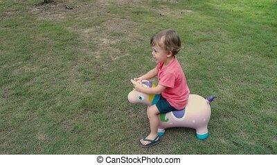 Cute little blonde boy riding on horse toy unicorn